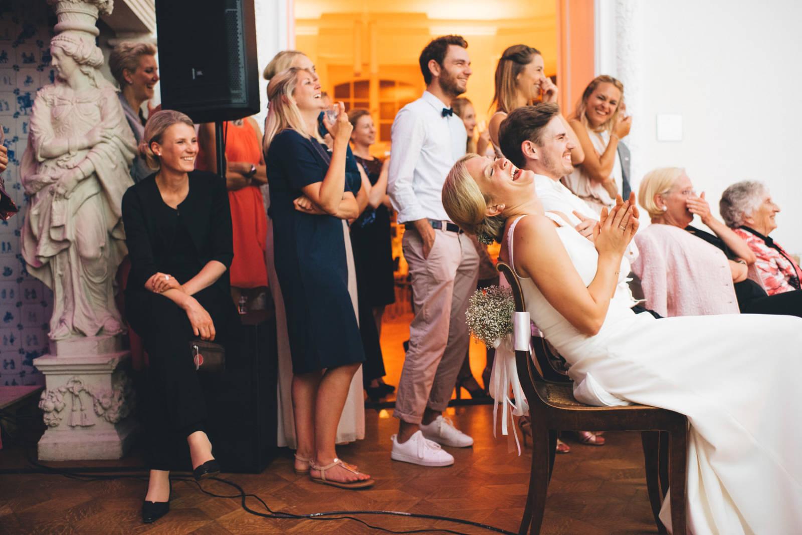 Brautpaar lacht herzhaft während der Feier bei einem Hochzeitsvideo ihrer Freunde Hochzeitsfotograf Basel
