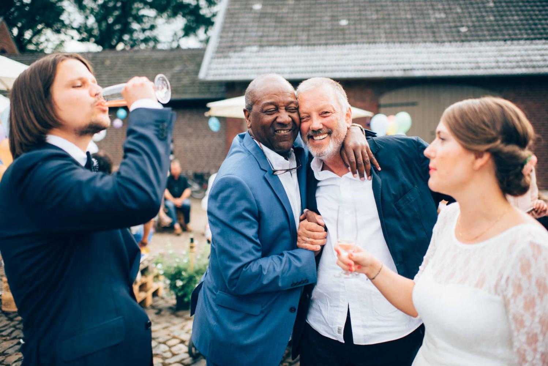 Brautpaar stößt auf der Party mit dem Bräutigamvater und Freunden an und freut sich Hochzeitsfotograf Stuttgart Baden-Württemberg Freiburg Heidelberg Schweiz Basel