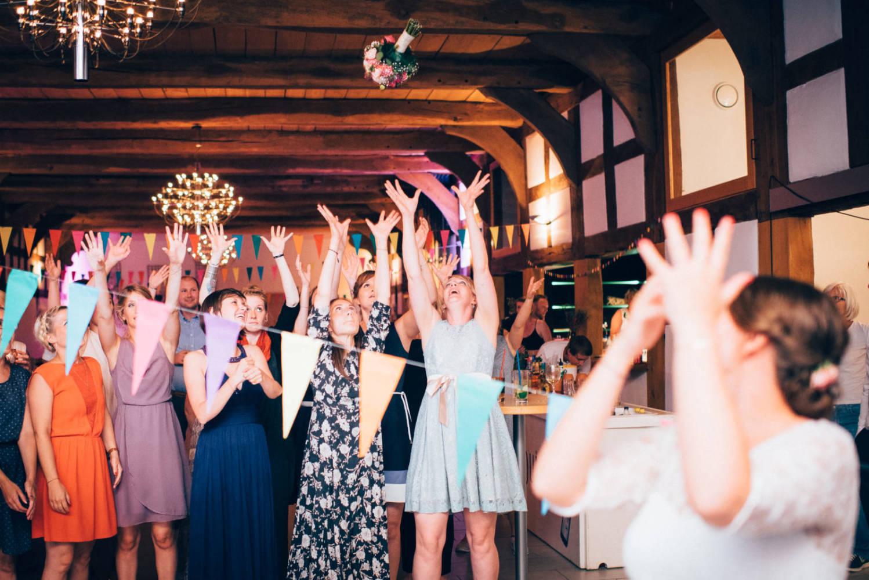 Die Braut wirft den Brautstrauß in die Menge der Frauen in der Nacht der Hochzeitsparty Hochzeitsfotograf Stuttgart Baden-Württemberg Freiburg Heidelberg Schweiz Basel