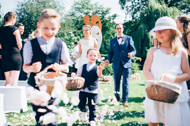 Auszug des Brautpaares nach der Freien Trauung im Garten umgeben von Blumenkindern Hochzeitsfotograf Baden-Württemberg Tübingen Bruno Biermann