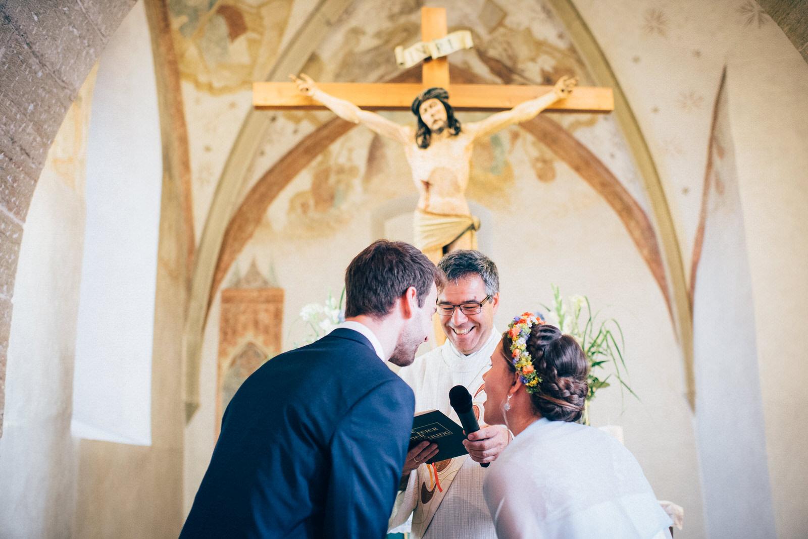 Ja-Wort bei der kirchlichen Trauung während der Priester lacht Hochzeitsfotografie Basel-Land